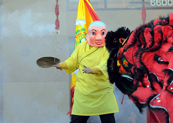 The Happy Buddha, Alexandra Ralat, guides the three lions through their dance as firecrackers go off at the entrance to the Pacific Ocean Marketplace in Broomfield on Sunday. Members of the Tai Kung Ha Holistic Fitness Center perform the Lion Dance to help bring in the Chinese New Year, the year of the Tiger.<br /> <br /> February 14, 2010<br /> Staff photo/David R. Jennings
