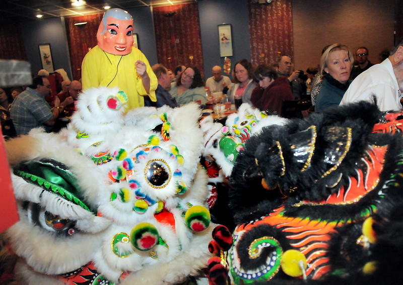 The Happy Buddha, Allen Tran, left, guides the yellow and red lions through the restaurant during the traditional lion dance performance by the Tai Kung Ha Holistic Fitness Center, at the United Chinese Restaurant in celebration of Chinese New Year, the year of the dragon, on Monday.<br /> January 23, 2012<br /> staff photo/ David R. Jennings