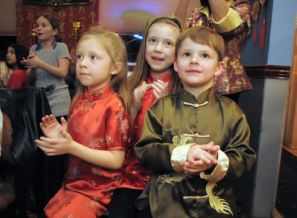 Ava Nordgren, 6, left, with her sister Gracie Nordgren, 10, and Cole Bialek, 5, watch magician Naiyi Zhao preform for Chinese New Year at United Chinese Restaurant on Monday.<br /> January 23, 2012<br /> staff photo/ David R. Jennings