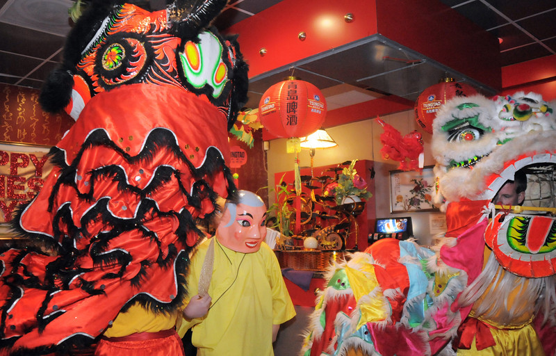 The Happy Buddha, Allen Tran, center, guides Thuan Tran, the red lion,  and Doug Sexton, the yellow lion, during the traditional lion dance performance by the Tai Kung Ha Holistic Fitness Center, into the United Chinese Restaurant to celebrate Chinese New Year, the year of the dragon, on Monday.<br /> January 23, 2012<br /> staff photo/ David R. Jennings