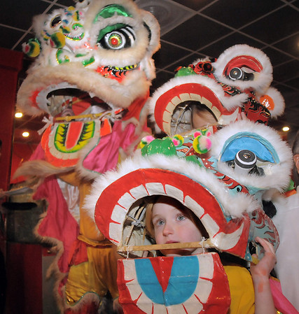 "Baby lion dancers Amy Hatchett, 6, front, and Gabbi Kovalenko, 10, right, with the yellow lion, Doug Sexton, watch the red lion perform a traditional dance for Chinese New Year at United Chinese Restaurant on Monday.<br /> For more photos please see  <a href=""http://www.broomfieldenterprise.com"">http://www.broomfieldenterprise.com</a><br /> January 23, 2012<br /> staff photo/ David R. Jennings"