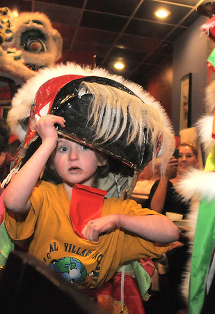 """Baby lion, Amy Hatchett, 6, peaks out from her costume during the traditional lion dance performance by the Tai Kung Ha Holistic Fitness Center, into the United Chinese Restaurant to celebrate Chinese New Year, the year of the dragon, on Monday.<br /> For more photos please see  <a href=""""http://www.broomfieldenterprise.com"""">http://www.broomfieldenterprise.com</a><br /> January 23, 2012<br /> staff photo/ David R. Jennings"""