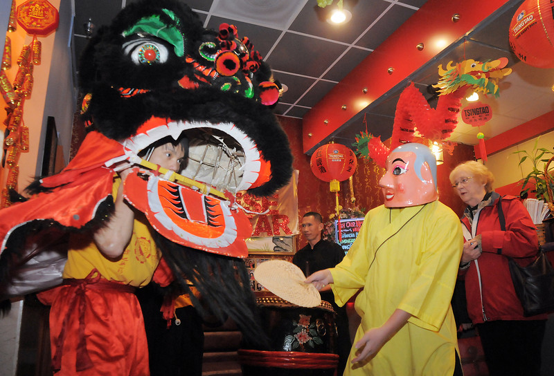 "The Happy Buddha, Allen Tran, right, guides Thuan Tran, the red lion, during the traditional lion dance performance by the Tai Kung Ha Holistic Fitness Center, into the United Chinese Restaurant to celebrate Chinese New Year, the year of the dragon, on Monday.<br /> For more photos please see  <a href=""http://www.broomfieldenterprise.com"">http://www.broomfieldenterprise.com</a><br /> January 23, 2012<br /> staff photo/ David R. Jennings"