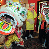 The Happy Buddha, Allen Tran, center, guides Doug Sexton, left, the yellow lion, and baby lions Gabbi Kovalenko, 10, and Amy Hatchett, 6, during the traditional lion dance performance by the Tai Kung Ha Holistic Fitness Center, into the United Chinese Restaurant to celebrate Chinese New Year, the year of the dragon, on Monday.<br /> January 23, 2012<br /> staff photo/ David R. Jennings