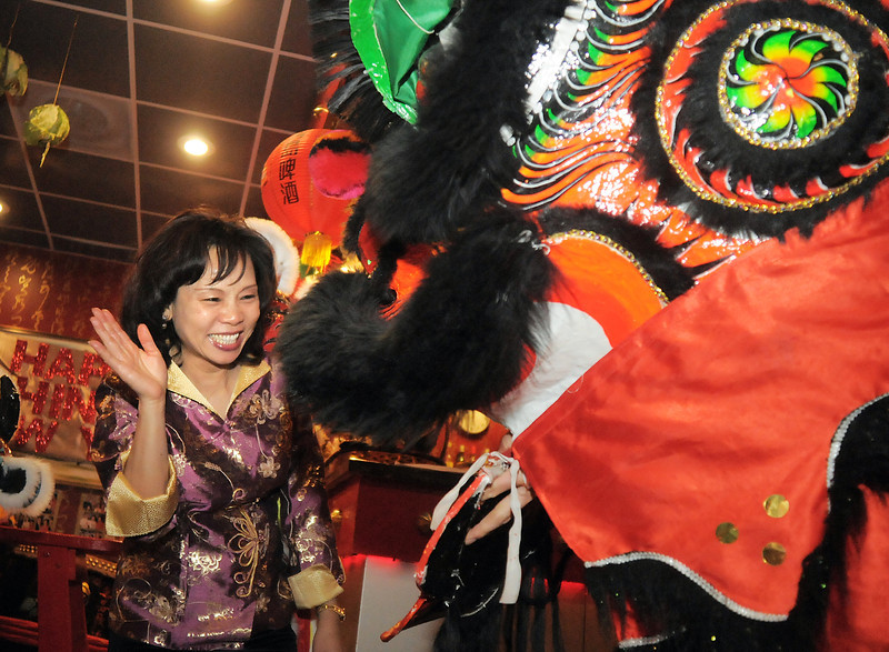 Melissa Chung, owner of  the United Chinese Restaurant, gives Thuan Tran, the red lion, a red envelope during the traditional lion dance performance by the Tai Kung Ha Holistic Fitness Center, for Chinese New Year, the year of the dragon, on Monday.<br /> January 23, 2012<br /> staff photo/ David R. Jennings