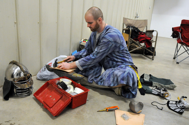 Syr Bjark GulBjornsson (Justin Hammons) works with leather for his helmet and gauntlets at the Society for Creative Anachronism meeting of the Barony of Caer Galen for Boulder and Broomfield counties at the Boulder County Fairgrounds in Longmont on Tuesday. <br /> <br /> <br /> January 12, 2010<br /> Staff photo/David R. Jennings