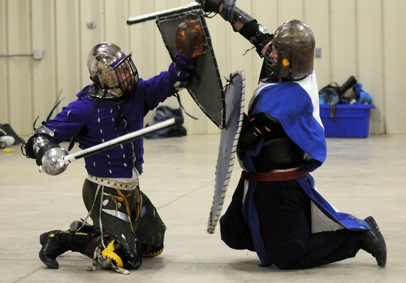 """Hans (Justin Wolff), left, and Argyle (Nick Solick of Denver) are on their knees while fighting denoting they've been """"injured"""" by a sword blow at the Society for Creative Anachronism meeting of the Barony of Caer Galen for Boulder and Broomfield counties at the Boulder County Fairgrounds in Longmont on Tuesday. Fighters use the honor system for acknowledging injuries during a fight.<br /> <br /> <br /> January 12, 2010<br /> Staff photo/David R. Jennings"""