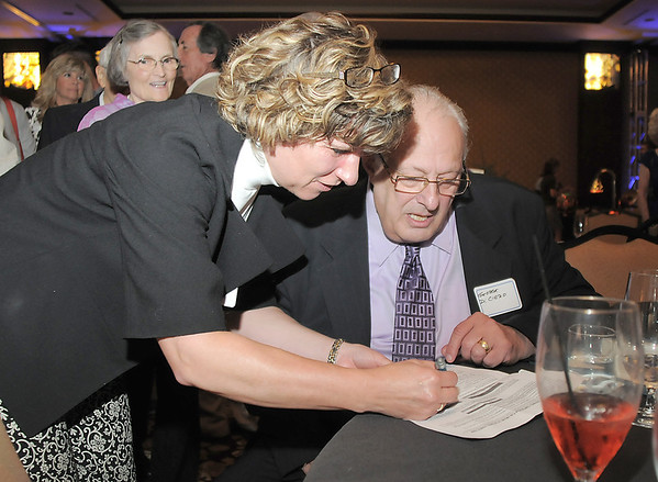 Suzanne Smith, director of human services, left , has retiring Broomfield City and County Manager George Di Ciero sign papers making his retirement official after the party in his honor, on Saturday, at the Omni Interlocken Hotel and Resort.<br /> July 30, 2011<br /> staff photo/ David R. Jennings