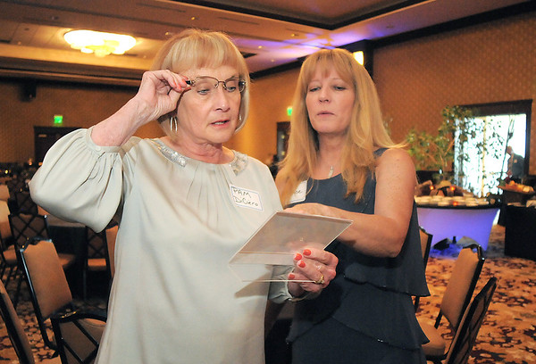 Pam Di Ciero, left, wife of George Di Ciero, and her daughter Denise Sevalt look at pictures of George Di Ciero, retired Broomfield City and County Manager during his retirement party, on Saturday, at the Omni Interlocken Hotel and Resort.<br /> July 30, 2011<br /> staff photo/ David R. Jennings