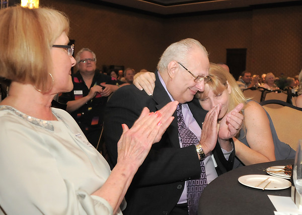 George Di Ciero, retired Broomfield City and County Manager is hugged by his daughter Denise Sevalt with his wife Pam, left, during Di Ciero's retirement party at the Omni Interlocken Hotel and Resort on Saturday.<br /> July 30, 2011<br /> staff photo/ David R. Jennings