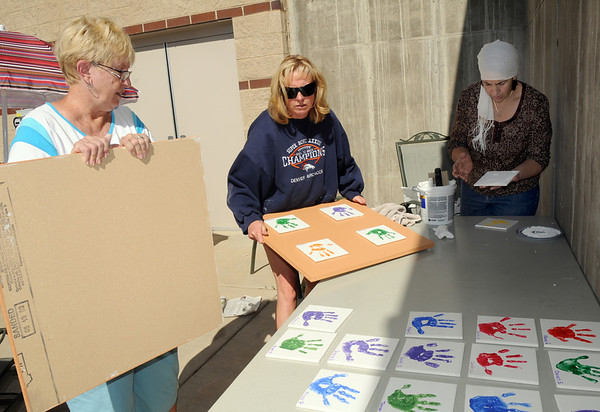 Bonnie King, left, Kim Evelsizer, and Siham Meharzi  attach hand prints of children on tiles to boards for display in the rec center during the cleaning and repair of the Derda Recreation Center on Thursday.<br /> <br /> August 27, 2009<br /> staff photo/David R. Jennings