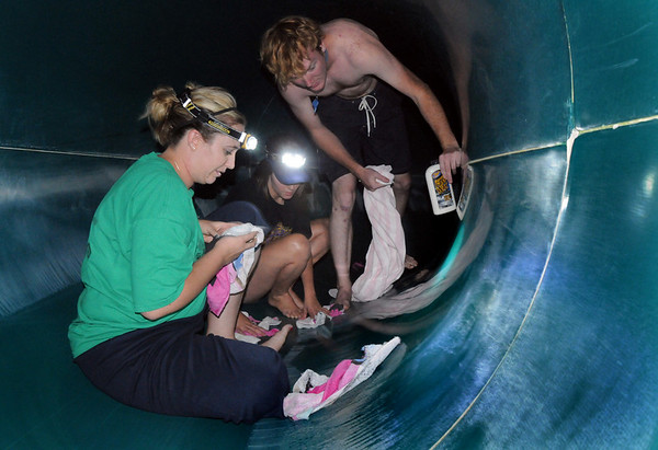 Brenda Wiegert, front, with fellow life guards Morgan Diller and Corey Davisson use head lamps to help the see as they clean and polish the tunnel section of the 136 foot long slide during the cleaning and repair work of the Derda Recreation Center on Wednesday.<br /> <br /> August 26, 2009<br /> staff photo/David R. Jennings
