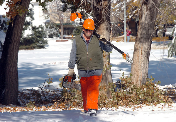 Chuck Gehringer, parks operations for the Broomfield City and County, carries his saws back to his truck after cutting tree branches that fell in Northmoor Park due to the October snow storm earlier this week.<br /> October 27, 2011<br /> staff photo/ David R. Jennings
