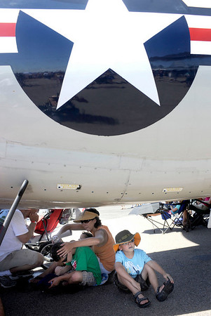 Luke Crumplar, 5, from right, his mother Joyce, brother Sean Jr., 8, sister Ava, 1, and father Sean Sn. all cool off in the shade of a large airplane during the Colorado Sport International Air Show on Saturday, Aug. 22, 2009 at the Rocky Mountain Metropolitan Airport in Broomfield.<br /> <br /> VIDEO INLINE: VIDEO: VIDEO: BROOM AIR SHOW 2009<br /> <br /> Photo by Mara Auster/Daily Camera