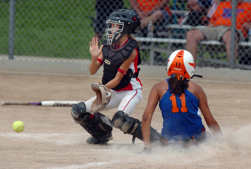 Texas Hawks catcher Kaitlyn Stavinoha watches the ball as Kourtni Vargas, Blaze Fastpitch, slides home during the 12U Colorado Fireworks Softball Tournament championship game between the Texas Hawks and Oklahoma BLaze Fastpitch at the Community Park ball fields on Sunday.<br /> <br /> July 4, 2010<br /> Staff photo/ David R. Jennings