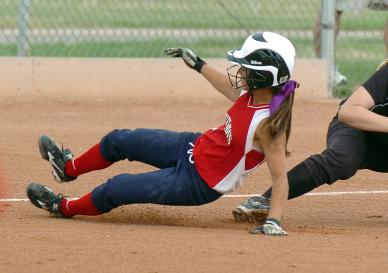 Texas Outlaws' Stephanie Money slides to third during the 14U Colorado Fireworks Softball Tournament championship game between the Texas Outlaws and Oregon Thunder at the Community Park ball fields on Sunday.<br /> <br /> July 4, 2010<br /> Staff photo/ David R. Jennings