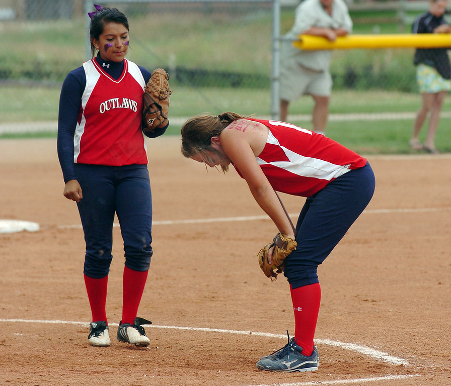 Texas Outlaws pitcher Kayla Ober, right, takes a moment from the game as third baseman Suzanne White talks to her during the 14U Colorado Fireworks Softball Tournament championship game between the Texas Outlaws and Oregon Thunder at the Community Park ball fields on Sunday.<br /> <br /> July 4, 2010<br /> Staff photo/ David R. Jennings