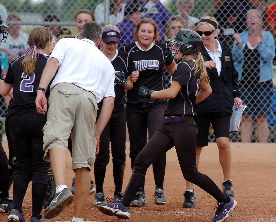 Ashlynn Schmitt, right, Oregon Thunder, readies to touch home plate as the team watches after hitting a home run during the 14U Colorado Fireworks Softball Tournament championship game between the Texas Outlaws and Oregon Thunder at the Community Park ball fields on Sunday.<br /> <br /> July 4, 2010<br /> Staff photo/ David R. Jennings