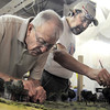 Broomfield Veterans Memorial Museum member Dr. Bill Markel, left,  glues foliage while Rod Postillion dusts small figures of Civil War soldiers on the diorama depicting Pickett's Charge at the Battle of Gettysburg at Fine Art Mannequins studio on Wednesday.<br /> July 6 2011<br /> staff photo/ David R. Jennings