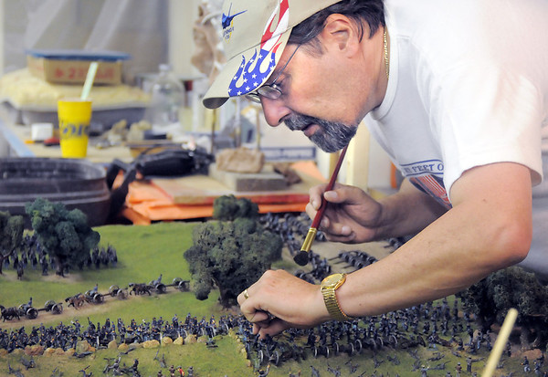 Rod Postillion arranges and re-glues small figures of Civil War soldiers on the Broomfield Veterans Memorial Museum diorama depicting the Pickett's charge at Fine Art Mannequins studio on Wednesday.<br /> <br /> July 6 2011<br /> staff photo/ David R. Jennings