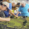 Rod Postillion, left, dusts small figures of Civil War soldiers off while  Broomfield Veterans Memorial Museum members Robert Davis, Marv Eakes and Dr. Bill Markel glue foliage on to the diorama depicting Pickett's Charge at the Battle of Gettysburg at Fine Art Mannequins studio on Wednesday.<br /> July 6 2011<br /> staff photo/ David R. Jennings