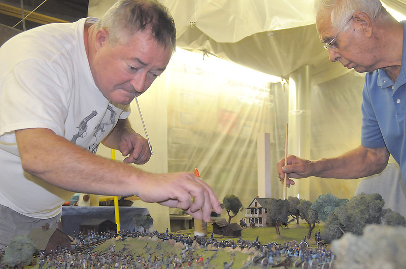 Kent Strapko, left, glues a small figure of Civil War soldier while Robert Davis dusts flock off of the figurines in the Broomfield Veterans Memorial Museum diorama depicting Pickett's Charge at the Battle of Gettysburg at Fine Art Mannequins studio on Wednesday.<br /> July 6 2011<br /> staff photo/ David R. Jennings