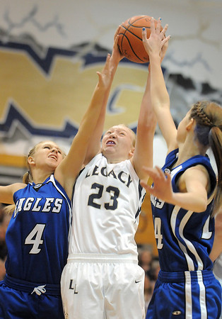 Legacy's Caitlyn Smith shoots the past  Broomfield's Morgan Rynearson and Meghan Stovall during Saturday's cross town game at Legacy.<br /> January 7, 2012<br /> staff photo/ David R. Jennings