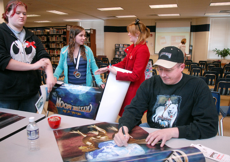 """Phillip """"Big Dog"""" Jones, author of the Worlds of the Crystal Moon, and alumnus of Broomfield High School signs a poster forJanell Fairchild, left,  Maggie Admire and Shelby Herman after speaking to students in the school library on Friday. <br /> <br /> April 16, 2010<br /> Staff photo/David R. Jennings"""