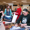 "Phillip ""Big Dog"" Jones, author of the Worlds of the Crystal Moon, and alumnus of Broomfield High School signs a poster forJanell Fairchild, left,  Maggie Admire and Shelby Herman after speaking to students in the school library on Friday. <br /> <br /> April 16, 2010<br /> Staff photo/David R. Jennings"