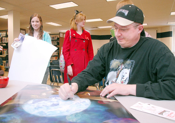 """Phillip """"Big Dog"""" Jones, author of the Worlds of the Crystal Moon, and alumnus of Broomfield High School signs a poster for Maggie Admire and Shelby Herman after speaking to students in the school library on Friday. <br /> <br /> April 16, 2010<br /> Staff photo/David R. Jennings"""