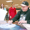 "Phillip ""Big Dog"" Jones, author of the Worlds of the Crystal Moon, and alumnus of Broomfield High School signs a poster for Maggie Admire and Shelby Herman after speaking to students in the school library on Friday. <br /> <br /> April 16, 2010<br /> Staff photo/David R. Jennings"