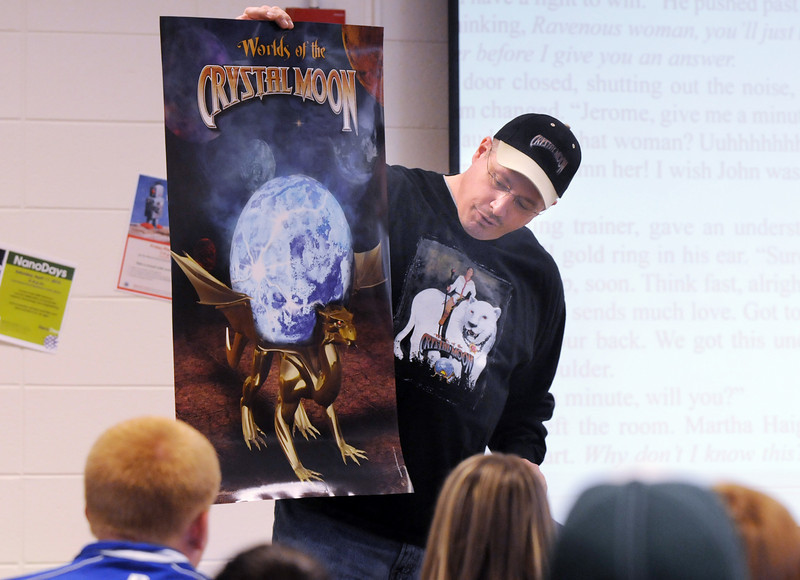 """Phillip """"Big Dog"""" Jones, author of the Worlds of the Crystal Moon, and alumnus of Broomfield High School shows one of two posters he has while speaking to students about his books in the school library on Friday. <br /> <br /> April 16, 2010<br /> Staff photo/David R. Jennings"""