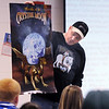 "Phillip ""Big Dog"" Jones, author of the Worlds of the Crystal Moon, and alumnus of Broomfield High School shows one of two posters he has while speaking to students about his books in the school library on Friday. <br /> <br /> April 16, 2010<br /> Staff photo/David R. Jennings"
