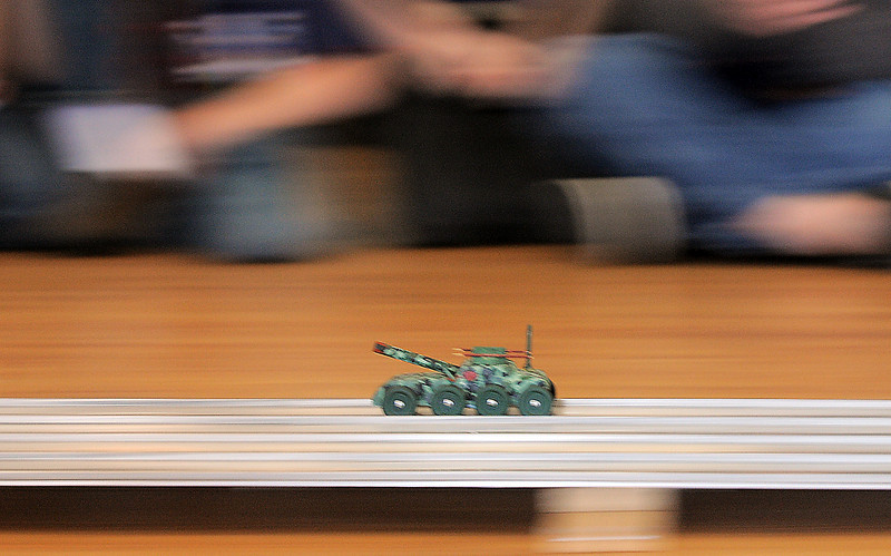A tank pinewood derby car streaeks past Cub Scouts watching Saturday's Pinewood Derby competition for Cub Scout Troop 586 held at the Broomfield Community Center.<br /> January 22, 2011<br /> staff photo/David R. Jennings