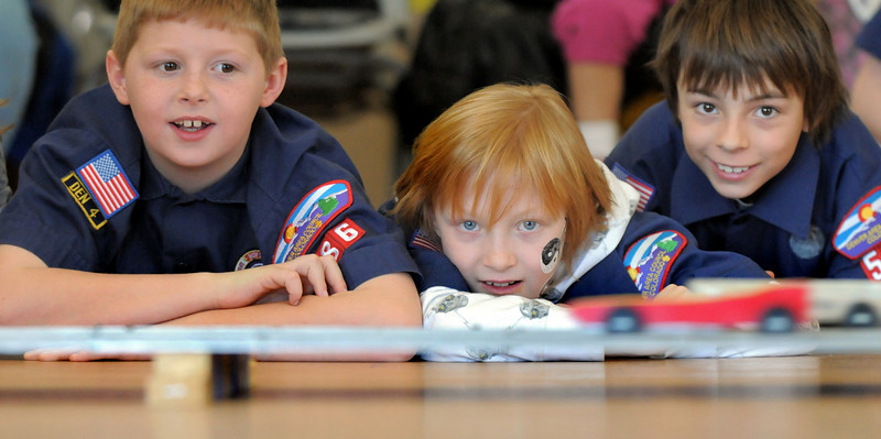 Cub Scouts Dylan Cannon, 8, left, Sully Shull, 9, and John Douthitt, 9, watch pinewood derby cars race past them during Saturday's Pinewood Derby competition for Cub Scout Troop 586 held at the Broomfield Community Center.<br /> January 22, 2011<br /> staff photo/David R. Jennings