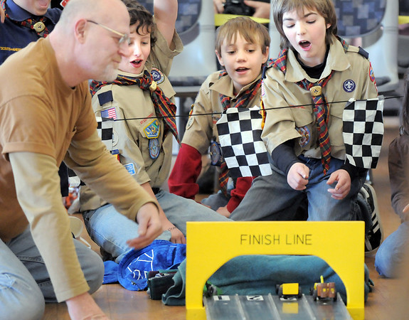 Steve Shull, left, finish line judge, watches cars end their race with Nick Page, 10, Dylan Messmer, 10, and Colin Hasbrook, 11, during Saturday's Pinewood Derby competition for Cub Scout Troop 586 held at the Broomfield Community Center.<br /> January 22, 2011<br /> staff photo/David R. Jennings
