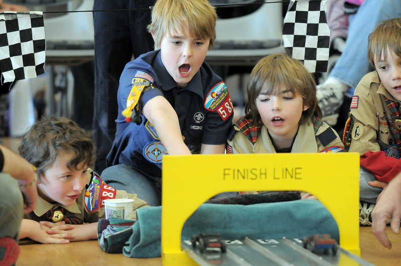 Nick Page, 10, left, Alex Pearson, 11, Colin Hasbrook, 11, and Dylan Messmer, 10, watch pinewood derby cars at the finish line during Saturday's Pinewood Derby competition for Cub Scout Troop 586 held at the Broomfield Community Center.<br /> <br /> January 22, 2011<br /> staff photo/David R. Jennings