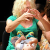 "Mary Lee Vice gestures to her grandson Jayden Vice, 9 months-old,  during the son ""Itsty bitsy spider"" at  Saturday's Cuddle Time Concert with professional pianist Jamie Grigsby playing Bach, Mozart, and Mother Goose at the Broomfield Audi.<br /> July 11, 2009<br /> staff photo/David R. Jennings"