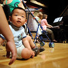 Jerry Liu, 21 months-old, sits on the floor while listening to Saturday's Cuddle Time Concert with professional pianist Jamie Grigsby playing Bach, Mozart, and Mother Goose at the Broomfield Audi.<br /> July 11, 2009<br /> staff photo/David R. Jennings