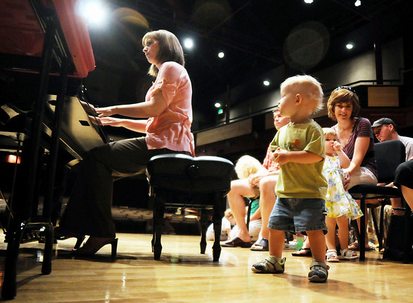 Jaden Davis, 19 months-old, right, dances to the music during Saturday's Cuddle Time Concert with professional pianist Jamie Grigsby playing Bach, Mozart, and Mother Goose at the Broomfield Audi.<br /> July 11, 2009<br /> staff photo/David R. Jennings