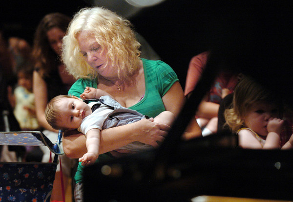 Mary Lee Vice holds her grandson Jayden Vice, 9 months-old, during the Cuddle Time Concert with professional pianist Jamie Grigsby playing Bach, Mozart, and Mother Goose at the Broomfield Audi.<br /> July 11, 2009<br /> staff photo/David R. Jennings