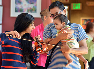 Archana Gopal, left, and her husband Ramesh show their daughter Saanui, 8 months-old, a violin after the Cuddle Time Concert with the Broomfield Symphony Orchestra on Saturday.  July 14, 2012 staff photo/ David R. Jennings