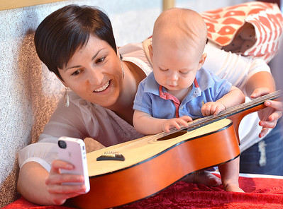 Brooke Priester, left, takes pictures of her son Caleb Alexander, 10 months-old, playing the guitar after the Cuddle Time Concert with the Broomfield Symphony Orchestra on Saturday.  July 14, 2012 staff photo/ David R. Jennings