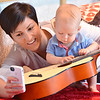 Brooke Priester, left, takes pictures of her son Caleb Alexander, 10 months-old, playing the guitar after the Cuddle Time Concert with the Broomfield Symphony Orchestra on Saturday.<br /> <br /> July 14, 2012<br /> staff photo/ David R. Jennings