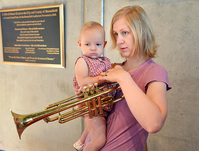 ryan Howard, right, looks at a trumpet with her daughter Cora, 15 months-old, after the Cuddle Time Concert with the Broomfield Symphony Orchestra on Saturday.  July 14, 2012 staff photo/ David R. Jennings  Ryan Howard and her daughter Cora, 15 months-old, 5ur5-u \
