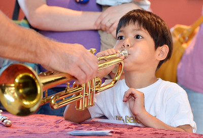 Alex Morreale, 5, tries blowing a trumpet after the Cuddle Time Concert with the Broomfield Symphony Orchestra on Saturday.  July 14, 2012 staff photo/ David R. Jennings