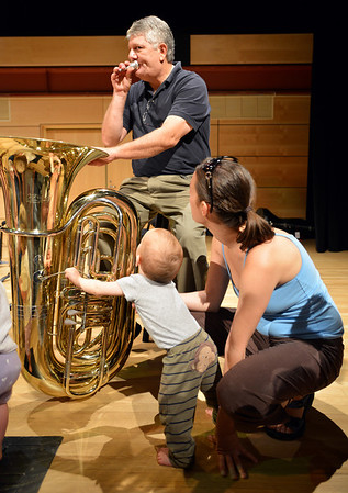 Tuba player Philip Houha demonstrates how to blow into the mouth piece to Adam Finkle, 10 months-old, and his mother Eva Pataki after the Cuddle Time Concert with the Broomfield Symphony Orchestra on Saturday.<br /> <br /> July 14, 2012<br /> staff photo/ David R. Jennings