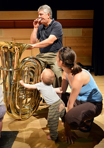 Tuba player Philip Houha demonstrates how to blow into the mouth piece to Adam Finkle, 10 months-old, and his mother Eva Pataki after the Cuddle Time Concert with the Broomfield Symphony Orchestra on Saturday.  July 14, 2012 staff photo/ David R. Jennings
