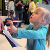 Caroline Scholpp, 3 1/2, looks at her mother holding Caroline's passport book  during Goddard School's cultural day on Friday.<br /> April 1, 2011<br /> staff photo/David R. Jennings