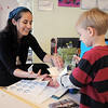 Maria Noelle Rivera de Jinenez , consulate agent for the Consulate General of Guatemala in Denver puts a sticker in Kylan Lints, 4, passport book during Goddard School's cultural day on Friday.<br /> April 1, 2011<br /> staff photo/David R. Jennings